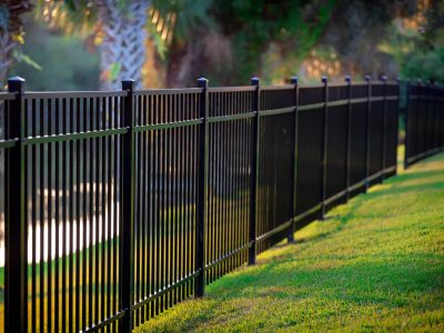 An image of a stylish and sturdy metal fence next to a lawn.